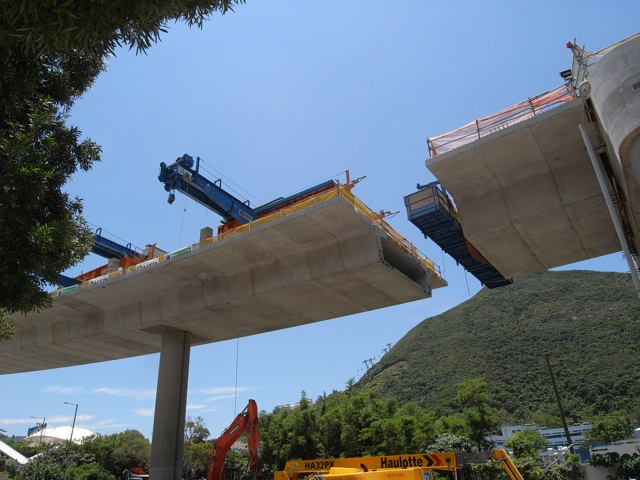 """At Wong Chuk Hang, the viaduct deck segments are pre-cast offsite and slotted into position using the """"beam-and-winch"""" equipment which is quieter to operate and generates less dust.  (Danny Chung)"""