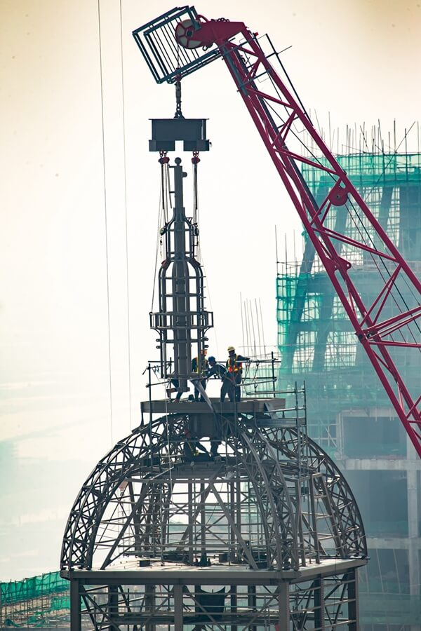 Photo caption: A crane places a lantern atop The Parisian Macao's Eiffel Tower at a topping out ceremony Thursday. Sands China's newest integrated resort and its half-scale replica Eiffel Tower are slated to open in the second half of 2016.
